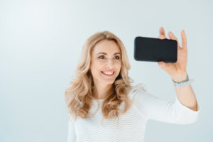 woman taking selfie showing off new smile.